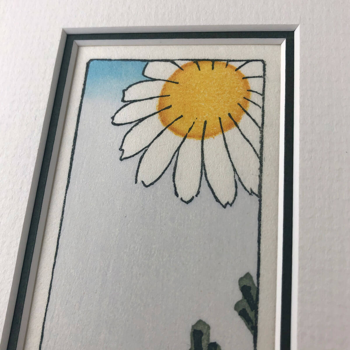 handmade woodblock print of a white daisy with yellow centre against pale blue grey background