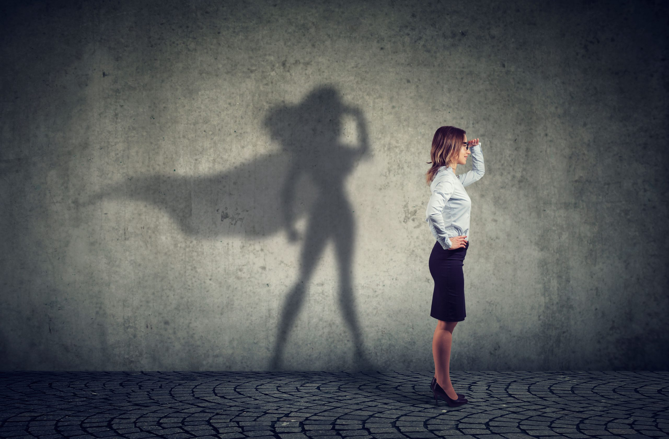 A lady is standing looking towards the right which represents CSMs looking towards a bright future. Her shadow shows a cape which represents Cami.AI, an ally/friend who enables her to improve her efficiency and productivity by equipping her with the necessary tools. Just like a superhero suit.
