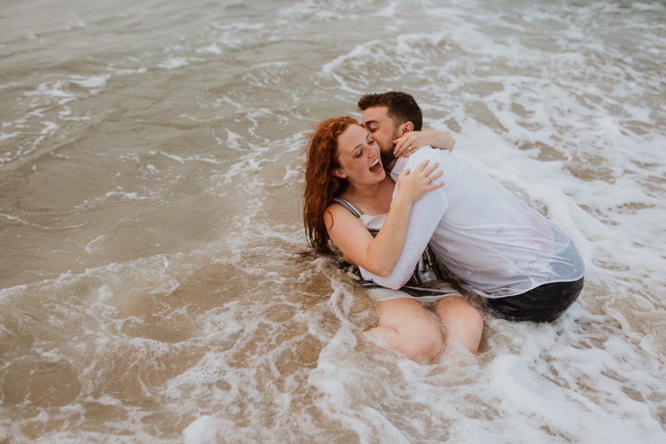 Couple on the beach in the water romantic engagement session avon North Carolina camille camacho photography