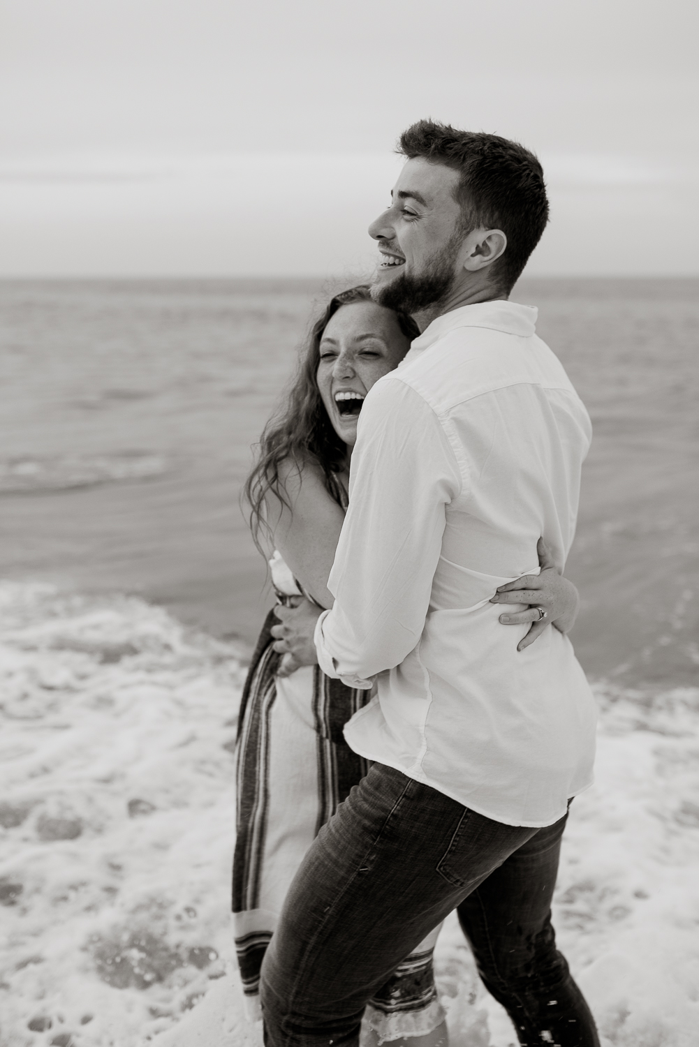 Couple on the beach in the water romantic engagement session black and white camille camacho photography