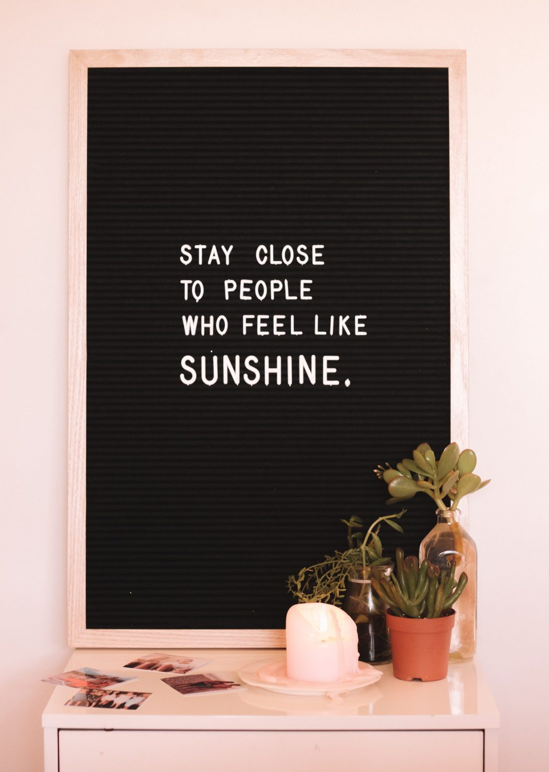 """Image of board and plants, with """"Stay close to people who feel like sunshine"""" quote."""