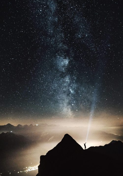individual shining light into the sky and finding meaning and their personal business in the stars