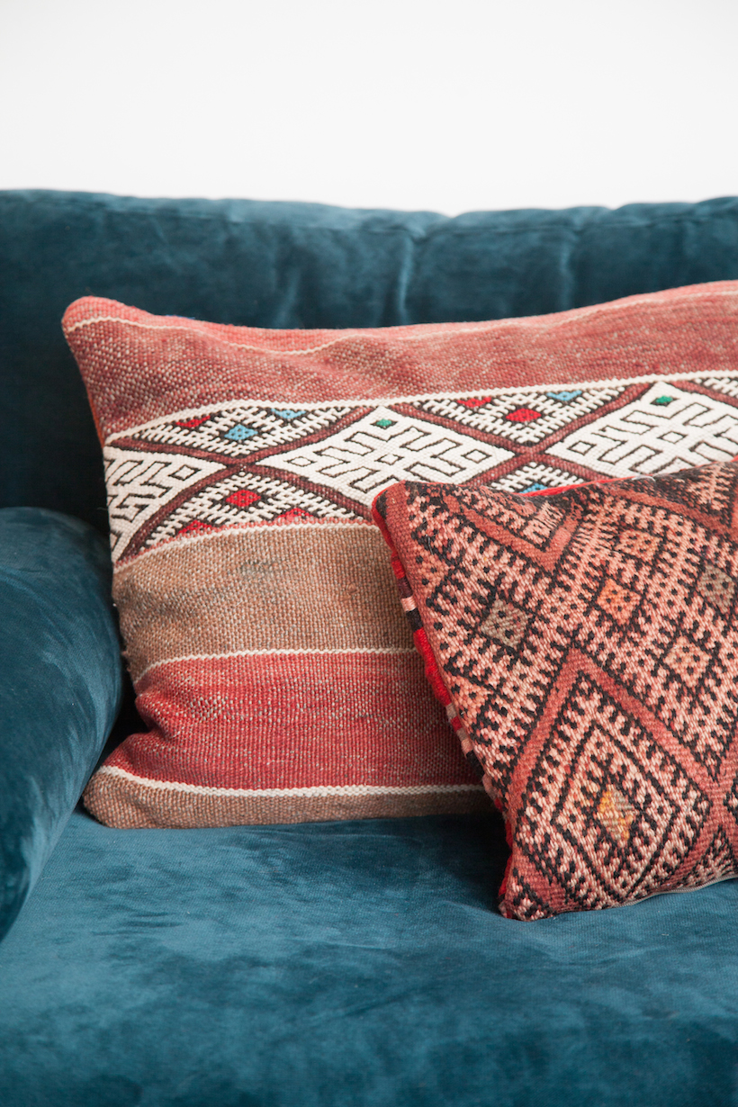 patterned pillows on bold blue couch