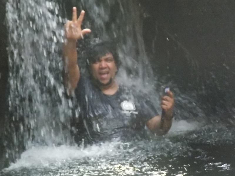 trindade e suas belezas naturais foto de homem em baixo de queda de agua - Trindade. Belezas naturais praias e cachoeiras em harmonia.