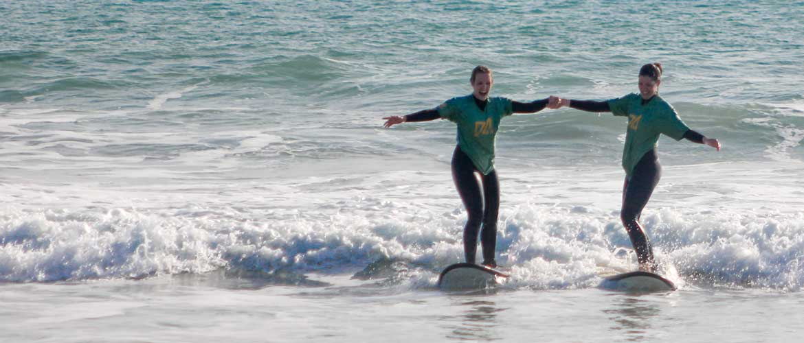 Camino Surfcamp Andalusien Two Surfing Girls Holding Hands