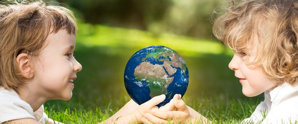 Children`s holding world in hands against green spring background. Earth day concept. Elements of this image furnished by NASA