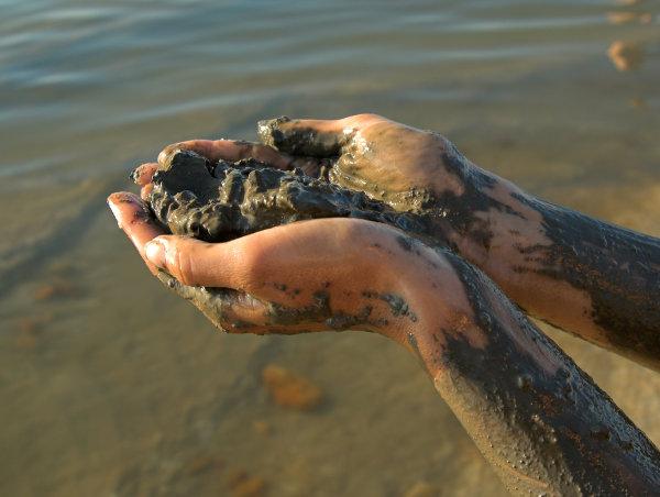 half naked woman add dead sea clay