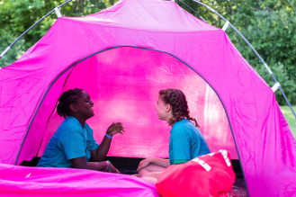 Two girls in a tent laughing