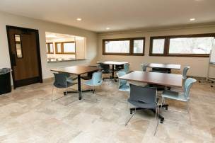 Tile floor room with windows, four tables and four chairs at each table. Classroom includes rolling whiteboard.