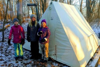 Three Girl Scouts standing outside their winter tent.
