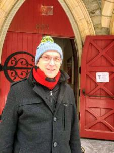 Dean Bertrand Olivier in front of Christ Church Cathedral's red doors.
