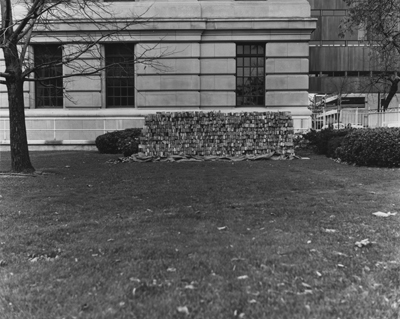 Black and white photograph of building materials on empty lot