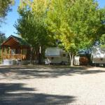 Shady camp sites next to the river at Outpost Motel, Cabins & RV Park