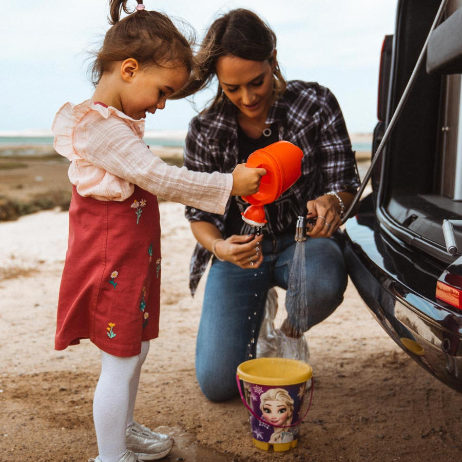 Family using the VW California shower set while camping.