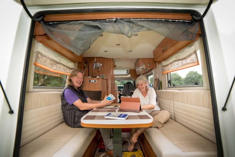 Dit zijn Walter Devenijns en Janine Stougie tijdens hun interview door het regionale dagblad de Stentor. Ze wonen en werken een groot deel van het jaar in camper Smuikje. Foto: Bram van de Biezen