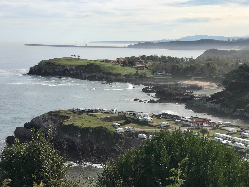 De Asturische kust bij het plaatsje en camping Perlora. Op de voorgrond zie de camping en over het water het vakantiedorp.