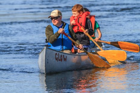 Adults and kids canoeing on the Puget Sound