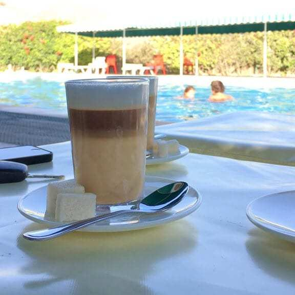 Delicious coffee Nous-Nous, which is typical for morocco, at the swimming pool of the campsite Camping Aourir