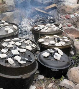 Dutch oven cooking taken to a great extent, six dutch ovens in a fire ring.