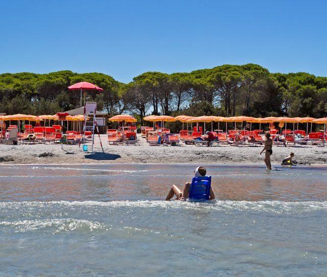 Turista Sulla Spiaggina In Mezzo Al Mare Nella Spiaggia Di Cala Ginepro In Sardegna