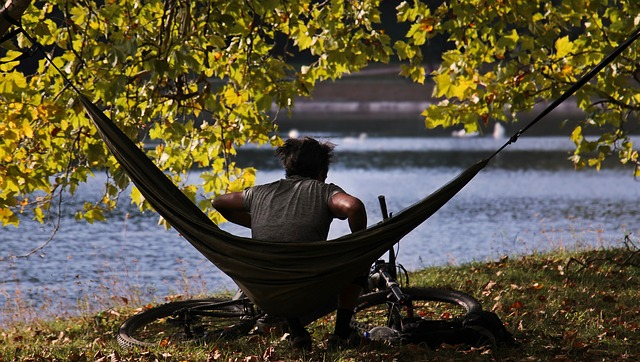 man sitting on a hammock along a river