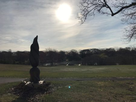 picture of the wooden phoenix statue with the sun in the sky over the pond