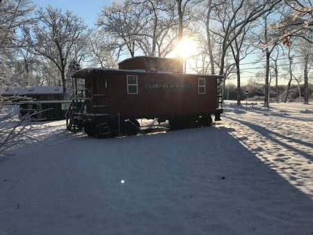 sun shining behind caboose covered in snow