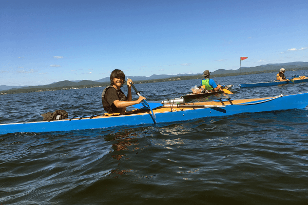 Image of boy smiling while paddling his kayak on Lake Champlain during Champlain Discovery, a Lake Champlain Maritime Museum summer expedition.