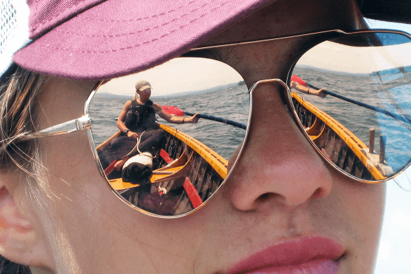 Image of a reflection on the sun glasses of an explorer, of another explorer passing an oar  during Expedition Champlain, one of the Lake Champlain Maritime Museum's summer expeditions.