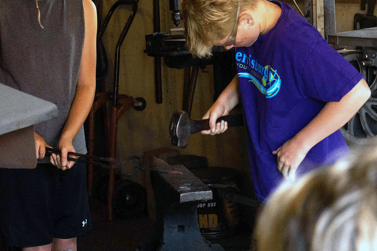 Image of a boy hammering hot iron on an anvil. LAC Summer Camps.