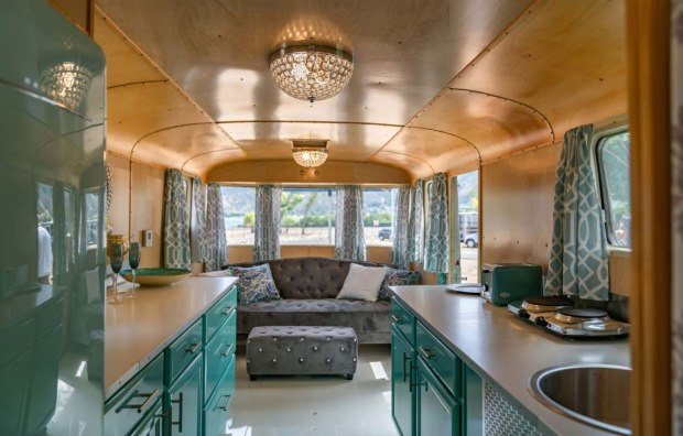 refurbished vintage camper with couch, teal cabinets, and wooden paneled walls