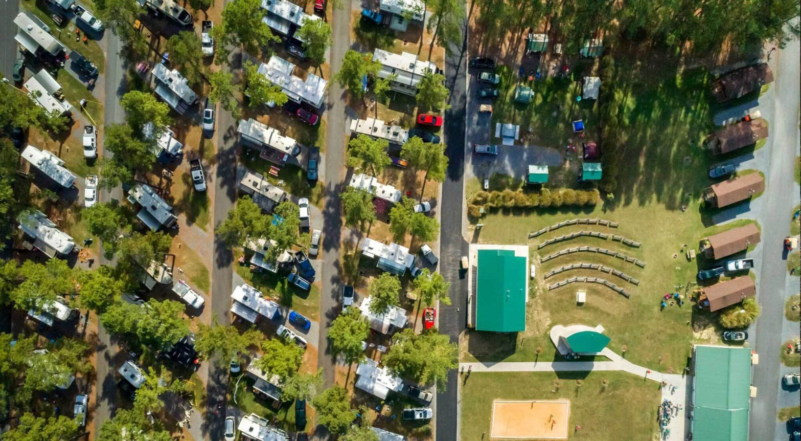 Aerial view of campground with paths lined with camping trailers and campsites