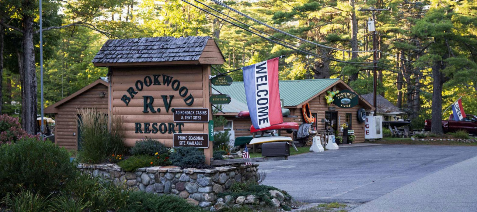 Campground wooden log sign with welcome flag and office building