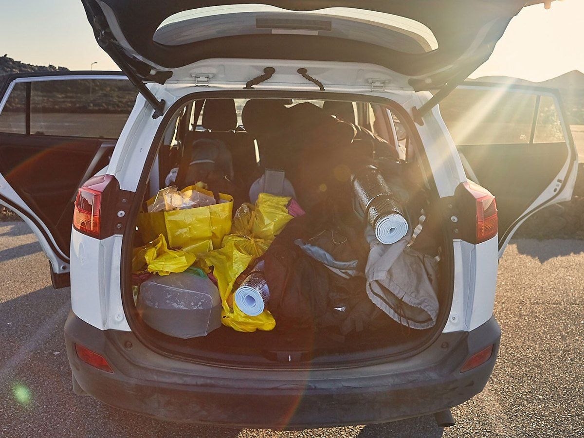 white car packed with camping items with trunk and doors opened