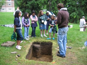 Campus Archaeologist Terry Brock explains the test unit