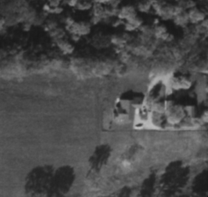 October 1953 aerial image of Toolan home lot, Hagadorn Road located just outside of the image to the right. Note the main house on the left, as well as the presence of one or two smaller outbuildings to the right of the main home.