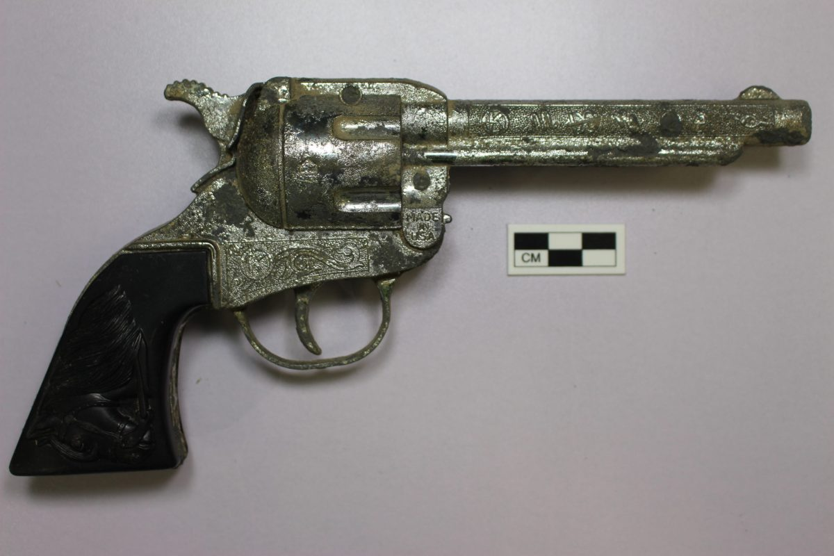 A chrome painted metal toy gun designed to look like a revolver. It is decorated with ranch and equine motifes.