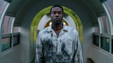 Candyman stands in dirty clothes in a symmetrical hallway
