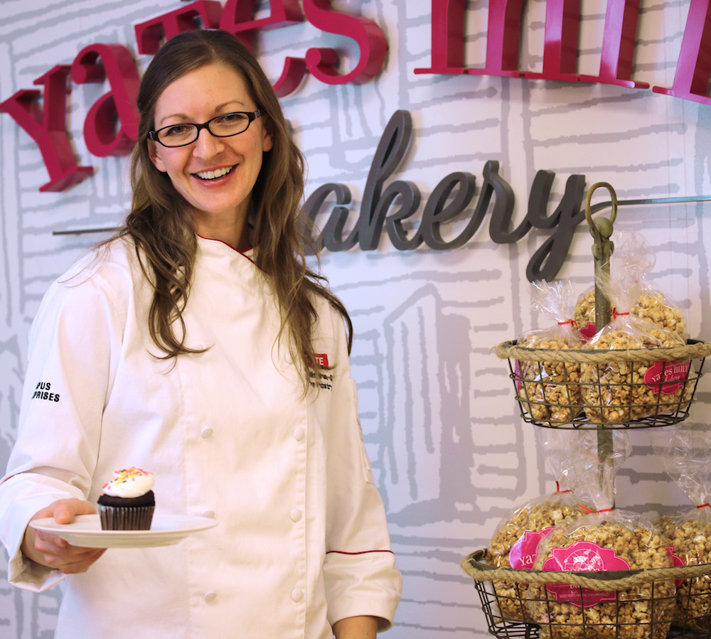 picture of chef Kelly holding a cupcake in front of yates mill logo