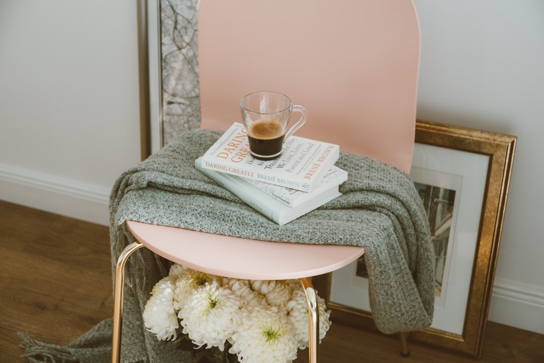 Pink chair with books and coffee cup