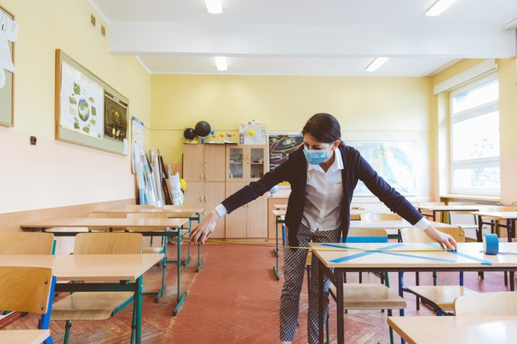 Teacher measuring distances between two desks with mask on