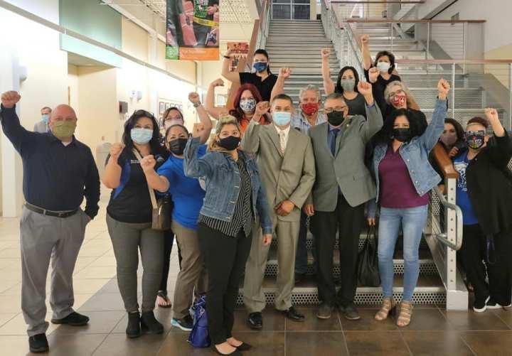 Socorro members lining staircase raising fists, wearing masks