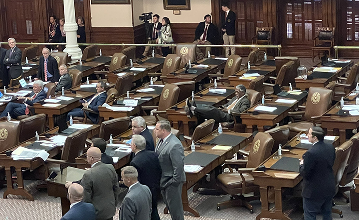 A wide photo of the Texas House chamber with remaining Republican legislators. Democrat Harold Dutton sits alone at a desk in the middle of the photo with his feet propped up.