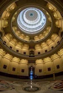 Rays from light in a distant door way dash through a darkened capitol rotunda
