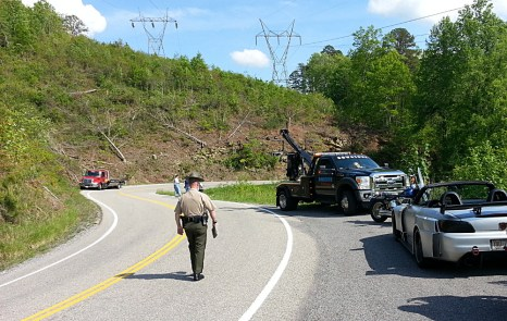 """""""Son, just how fast were you going, trying to show off for the camera?"""" - a state trooper inspects the scene of an accident, after a biker sends his cruiser over a cliff. Thankfully, he was all right. Photo: Zac Kurylyk"""