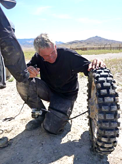 Warren fixes a flat, in the middle of nowhere.
