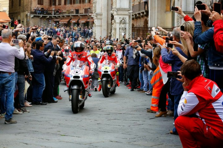 Drama! Heros Dovizioso and Iannone cruise down a Tuscan medieval street to adoring throngs.  License, insurance and road legal motorcycles are optional