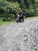 Zac rolls his broken bike downhill to seek cover from the rain. Photo: Chris Nielsen