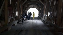 Shame! Zac hangs out at the Forty Five River covered bridge with some other riders, who took pity on his lack of preparation and shared their granola bars with him. Photo: Ken Smith