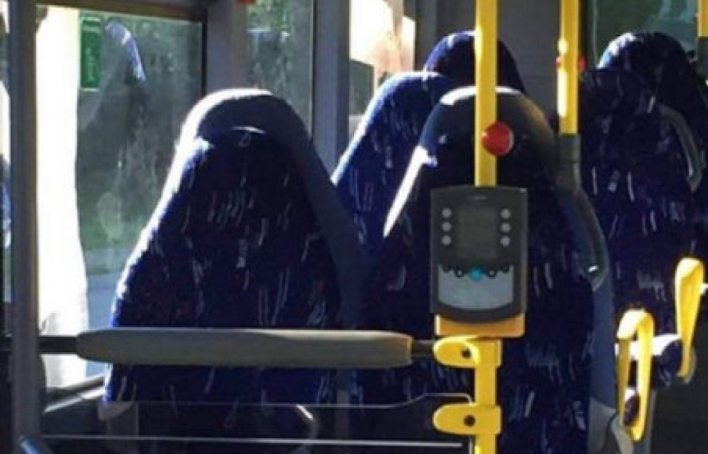 [A photo of the interior of a bus with empty seats. Due to a trick of the light, some people have misinterpreted the seats as seated women wearing burqas.]